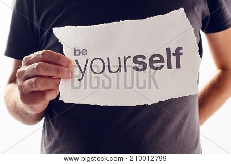 Man holding paper with Be Yourself motivational message