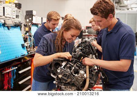 Apprentice car mechanics working on an engine