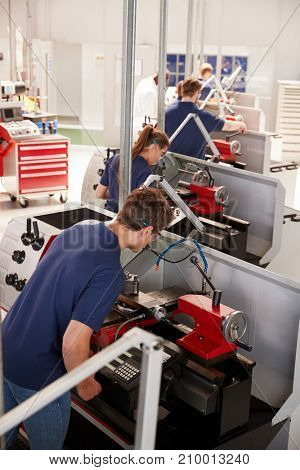 Trainee engineers operating equipment in a factory, vertical