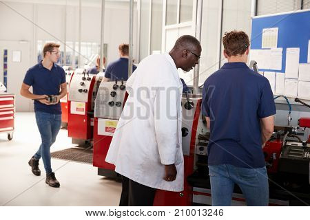 Engineer overseeing an apprentice at his workstation