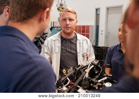 Car mechanic listening to questions from apprentices