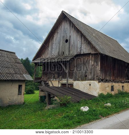 Typical traditional Alpine barn shed located in Slovenian touristic village Ribcev laz next to the Bohinj lake poster