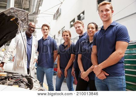 Car mechanic and apprentices in a garage looking to camera