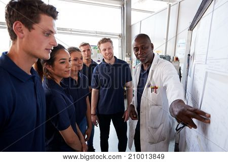 Engineer pointing to whiteboard while training apprentices