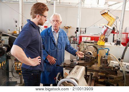 Senior engineer talking to apprentice at machine bench