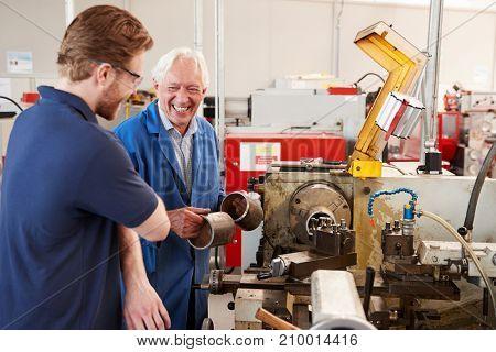 Smiling senior engineer talking with apprentice