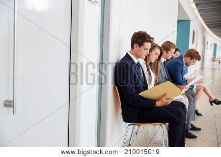 Five young candidates sit waiting for job interviews