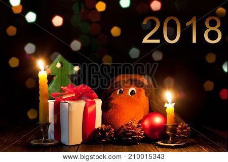 New year's night. Celebratory lights. Gifts and the symbol of the year. Christmas decorations and candles. Dark Background.
