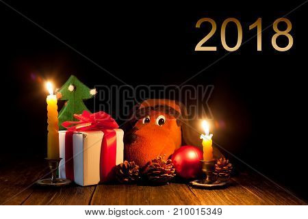 New year's night - celebratory lights. Gifts and the symbol of the year. Christmas decorations and candles. Dark Background.