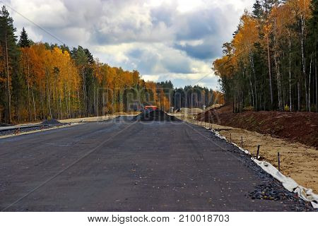 construction of a new highway on the background of an autumn landscape with a beautiful sky