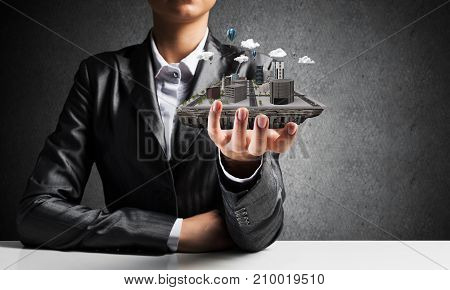 Cropped image of businessman in suit presenting in his hand modern city block with gray wall on background. 3D rendering.