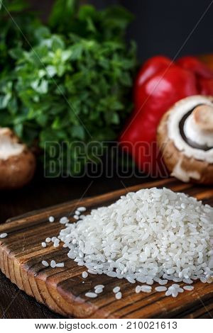 Wooden kitchen board with the rice on it, arounded by vegetables and spices