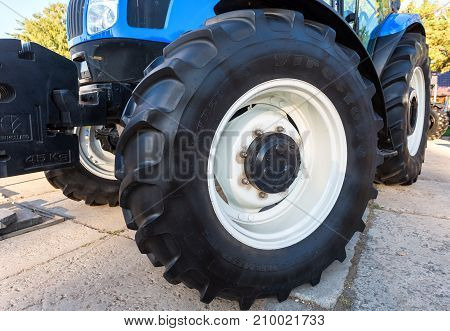 Russia Samara - September 23 2017: Big wheel of new modern agricultural tractor New Holland on display at the annual Volga agro-industrial exhibition