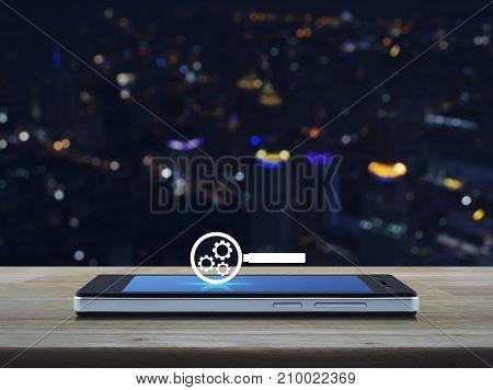 seo flat icon on modern smart phone screen on wooden table over blur colorful night light city tower Search engine optimization concept