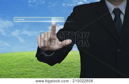 Businessman hand pressing search www button over green grass field with blue sky Searching system and internet concept