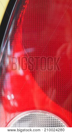 Car (Chinese) tail lights brake left red color is cracking inside Photo close up see detail and texture full frame.
