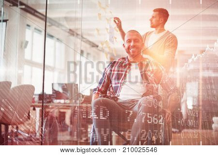 Stocks and shares against portrait of smiling handicap businessman in creative office