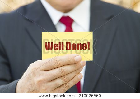 Businessman showing a card with text WELL DONE.