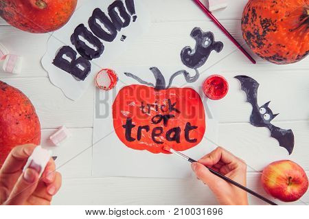 Halloween holiday background. Female hands draws decoration. Prepearing for party. Fresh pumpkins, candies, art, craft and painting materials on white table. Selective focus, top view. Space for text.