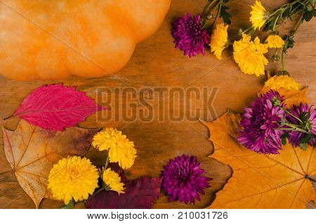 Pumpkin violet and yellow chrysanthemum flowers and dry autumn leaves on a worn wooden background selective focus on the autumn flowers and leaves (copy space in the center top view flat lay) retro style