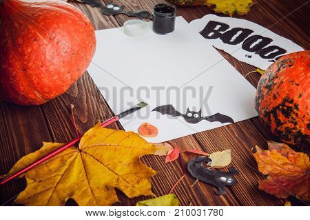 Halloween holiday background. Prepearing for party. Fresh pumpkins, coloured leaves, art, craft and painting materials on dark wooden table. Selective focus, top view. Space for text.