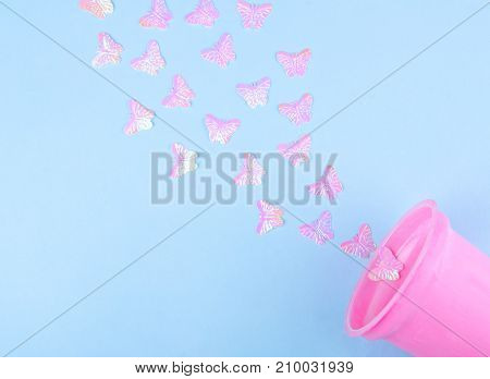 Beautiful pink artificial butterflies flying out of a pink plastic glass (on a blue paper background) minimal concept flat lay with copy space on the left