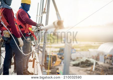 Construction workers wearing safety harness belt during working at height in the construction site area.