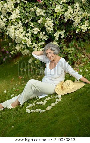 beautiful  woman posing near tree with  flowers outdoors