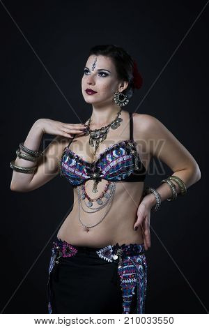 Women performs belly dance in ethnic dress on black background studio shot