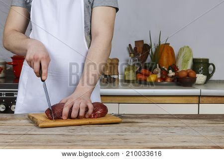 Man In The Kitchen Cutting A Piece Of Meat