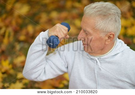 Senior man doing exercises with dumbbell in autumnal park