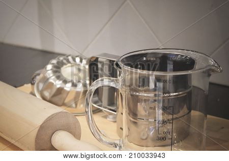 Kitchen Utensil Wooden Rolling Pin with Glass Measuring Cup and Cake Molds on A Wooden Cutting Board Used to Make Bakery Products.