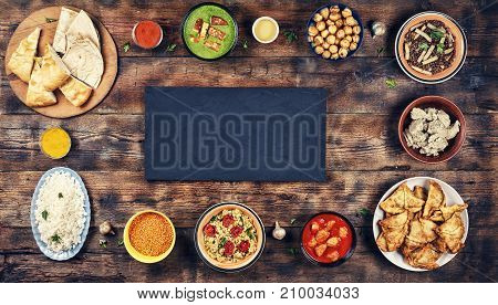 Assorted indian food on a wooden background. Dishes and appetizers of indian cuisine. Curry butter chicken rice lentils palak paneer samosa naan chutney spices. Bowls and plates with indian food