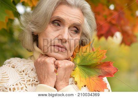 portrait of beautiful sad senior woman outdoors