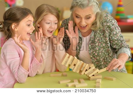 Two little girls and their grandmother playing with wooden plastic blocks