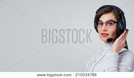 Young woman call center operator in headset on business office background.