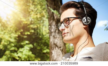 Close up Young Man Listening to his Favorite Music Using Headphone at the Park, Using MP3 Player