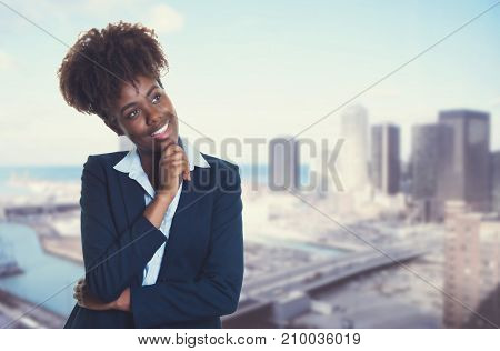 Thinking african american businesswoman with skyline of city in the background
