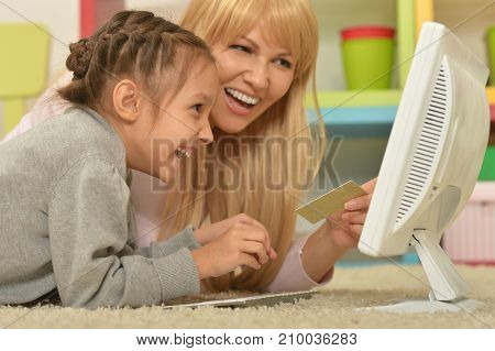 Mother and daughter using computer together while lying on floor