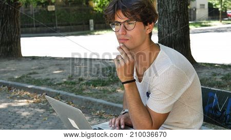 Handsome young man sitting on a wooden bench working outdoors in an urban park typing information onto his laptop computer