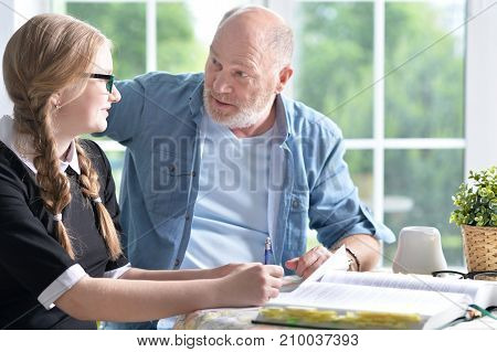 Grandfather and granddaughter doing homework together at home