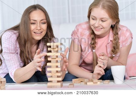 Mother and daughter playing with wooden blocks while sitting at table