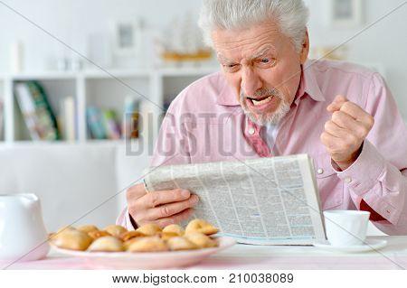 handsome senior man reading newspaper at kitchen
