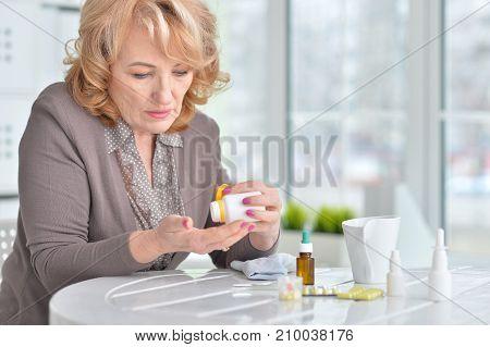 Sick senior woman taking medicines at home