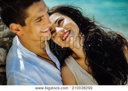 The girl loves looking at her boyfriend,against a background of blue water