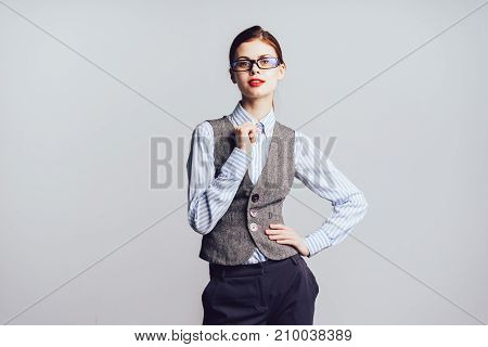 young modern successful girl in gray office vest and glasses keeps looks attractive