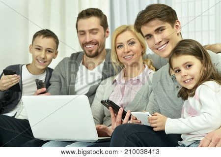 Family sitting on couch with laptop and other devices
