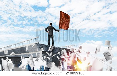 Rear view of confident businessman in suit holding flag in hand while standing among flying papers on broken bridge with cityscape and sunlight on background. 3D rendering.