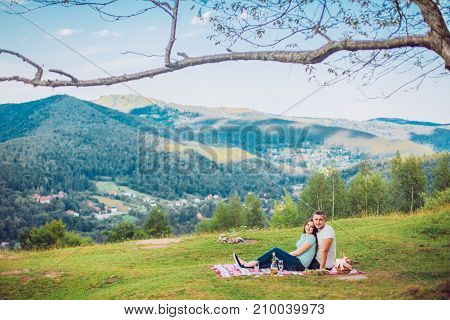 Couple in love on a white and red plaid in a field on a picnic. against a background of a mountains. romantic moment. Man and woman with champagne glass.