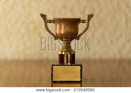 A small trophy on a brown table